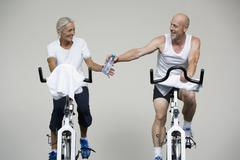 Stock Photo of A senior woman and a mature man riding stationary bikes and passing a water