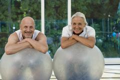 A mature man and a senior woman leaning on exercise balls Stock Photos
