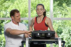 A fitness instructor helping a young woman on a treadmill Stock Photos