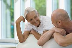 A mature man and a senior woman leaning on exercise balls - stock photo