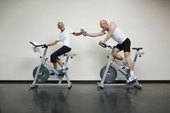 A senior woman and a mature man riding stationary bikes and passing a water Stock Photos
