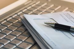A laptop keyboard with a stack of bills and a pen on it Stock Photos