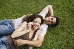 A young couple snuggling on a lawn Stock Photos