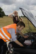 A mechanic repairing a woman's car at the roadside - stock photo