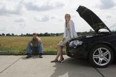 A couple waiting at the roadside for assistance with their car - stock photo