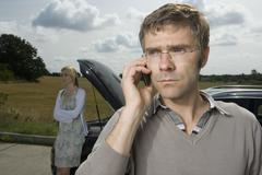A couple standing at the roadside next to their broken down car - stock photo