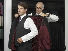 A tailor assisting a man trying on a suit Stock Photos