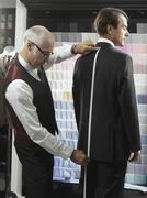 A tailor fitting a man with a suit Stock Photos