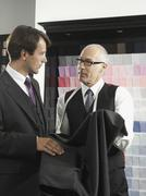 A tailor fitting a man with a suit - stock photo