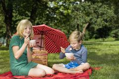 Two children eating strawberries and yogurt at a picnic - stock photo