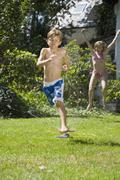 Two children playing in a sprinkler Stock Photos