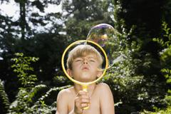 A boy blowing a bubble with a bubble wand Stock Photos