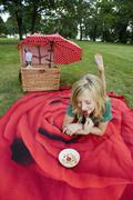 A girl with a bowl of yogurt, granola & strawberries at a picnic - stock photo