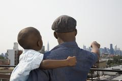 A father holding his son on a balcony Stock Photos