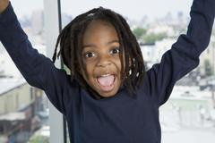 A young boy with his arms raised in excitement Stock Photos