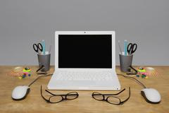 Laptop and stationary arranged on a desk - stock photo