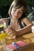 A young girl pouring herself a glass of juice, outdoors Stock Photos