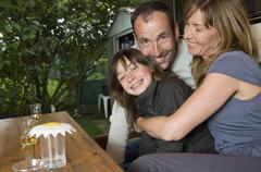 A family sitting at a table outside of their caravan - stock photo