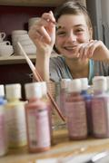 A girl giggling and pointing a paintbrush - stock photo