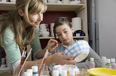 A mother helps her daughter at a pottery studio - stock photo