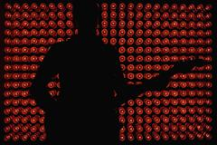 Silhouette of a musician standing in front of red lights Stock Photos