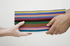 Human hands exchanging stack of multi colored paper Stock Photos