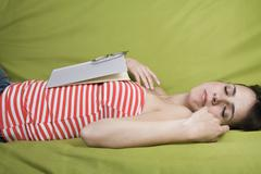 A Latin American woman sleeping with a book on her chest - stock photo