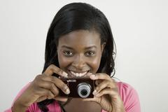 An african american woman preparing to take a photograph Stock Photos