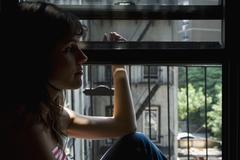 A Latin American woman sitting in a window sill Stock Photos