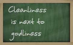 """ cleanliness is next to godliness "" written on a blackboard - stock photo"
