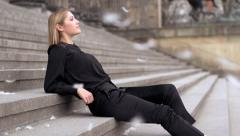 Beautiful blond women model black dress outside feathers slow motion Stock Footage