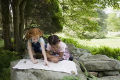 Two young girls reading a map, outdoors Stock Photos