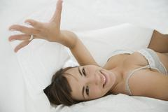 A woman lying under bed covers - stock photo