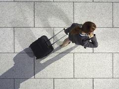 A businesswoman pulling a suitcase and talking on her mobile phone Stock Photos