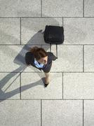 A businesswoman pulling a suitcase Stock Photos