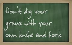 """ don't dig your grave with your own knife and fork "" written on a blackboard - stock photo"