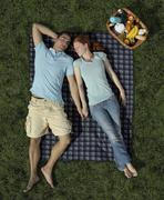 A young couple sleeping on a blanket in the park - stock photo
