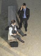 Stock Photo of Two businessmen waiting by a bench