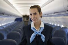 A flight attendant standing in the cabin of a plane - stock photo
