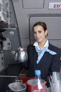 A flight attendant holding a coffee pot in an airplane galley Stock Photos