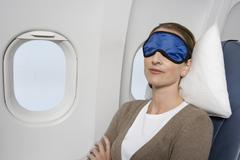 A woman wearing a sleep mask sleeping on a plane - stock photo