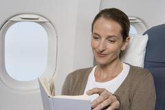 A female passenger reading on a plane Stock Photos