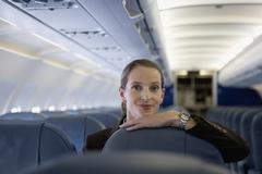 A woman resting her chin on the top of an airplane seat - stock photo