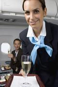 A flight attendant serving champagne Stock Photos