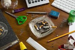 An office desk cluttered with office supplies and ashtrays Stock Photos