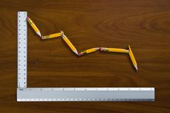 A line graph showing decline made from pencils and rulers Stock Photos