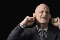 A man blocking his ears with his fingers Stock Photos
