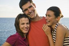 Three friends sharing a laugh by the sea Stock Photos