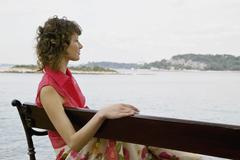 A woman sitting on a bench looking out at the sea Stock Photos
