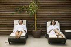 Two women lying in lounge chairs Stock Photos